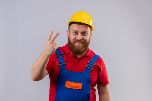 Young bearded builder man in construction uniform and safety helmet looking at camera smiling showing and pointing up with fingers number two or victory sign