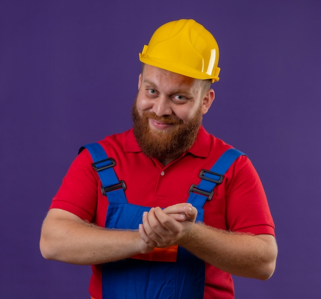 Young bearded builder man in construction uniform and safety helmet looking happy and positive holding arms together over purple background