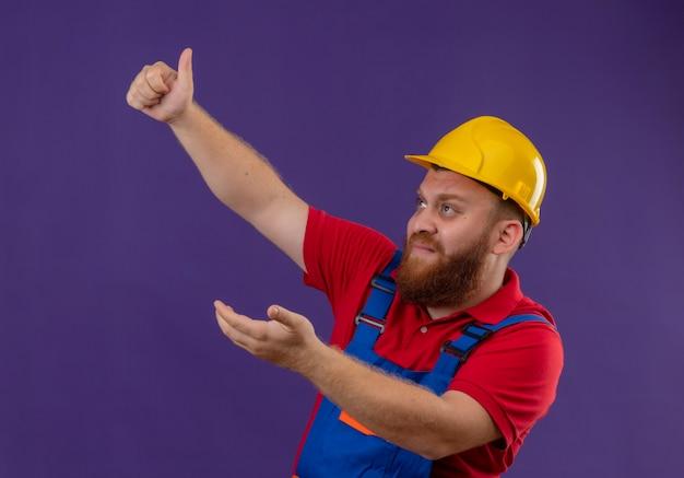 Giovane barbuto uomo costruttore in uniforme da costruzione e casco di sicurezza che osserva in su con l'espressione di paura che mostra i pollici in su su sfondo viola