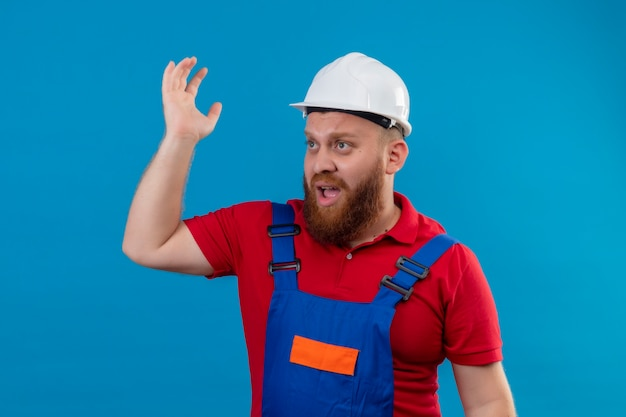 Young bearded builder man in construction uniform and safety helmet shouting looking confused raising hand