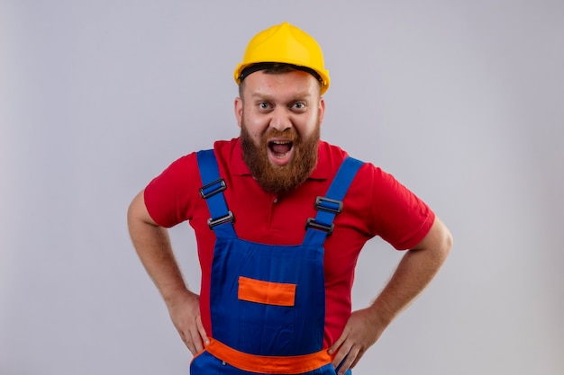 Young bearded builder man in construction uniform and safety helmet shouting with aggressive expression
