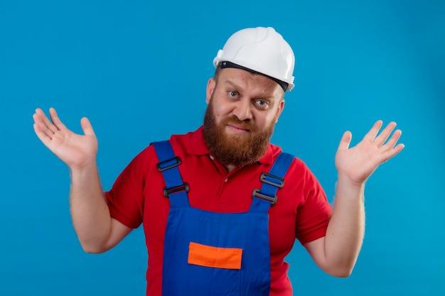 Giovane barbuto uomo costruttore in uniforme da costruzione e casco di sicurezza che scrolla le spalle, guardando confuso e incerto, senza risposta, allargando le palme