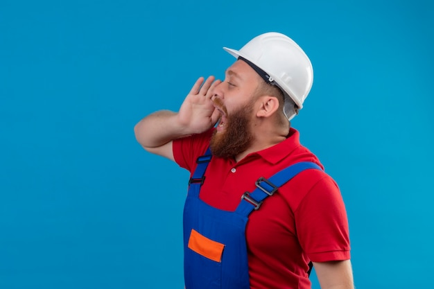 Young bearded builder man in construction uniform and safety helmet sideways shouting or calling someone with hand near mouth