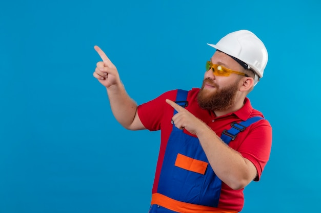 Young bearded builder man in construction uniform and safety helmet smiling happy and positive pointing with fingers to the side