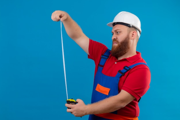 Young bearded builder man in construction uniform and safety helmet using measurement tape looking at it with serious face