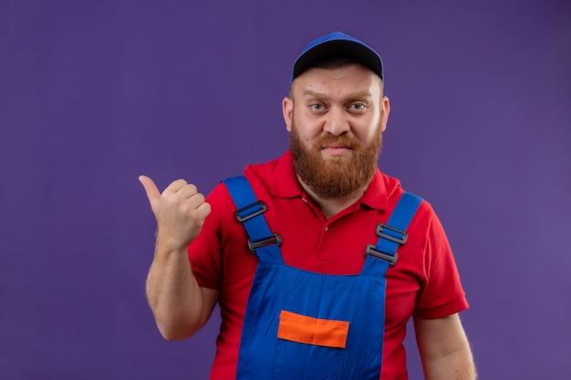 건설 유니폼과 모자에 젊은 수염 작성기 남자 보라색 배경 위에 손가락으로 가리키는 불쾌