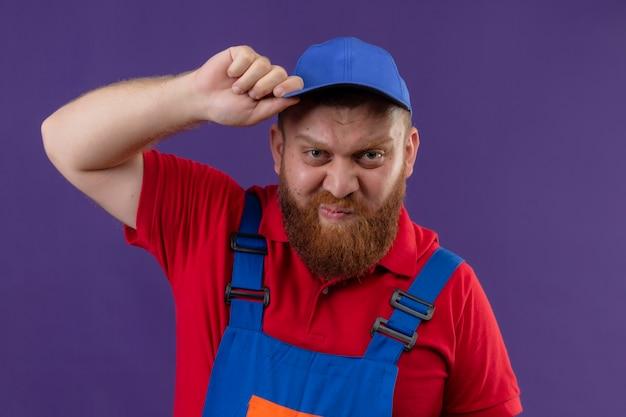 건설 유니폼과 모자에 젊은 수염 작성기 남자는 보라색 배경 위에 그의 모자를 만지고 불쾌