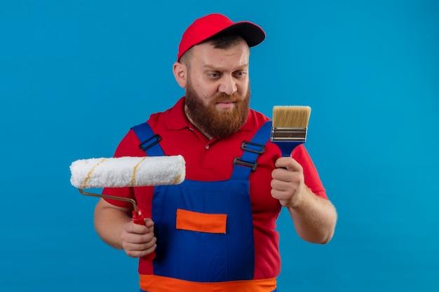 Молодой бородатый строитель в строительной форме и кепке держит валик и кисть, глядя на кисть со скептическим выражением лица