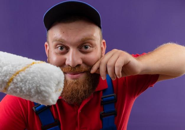 紫色の背景に笑みを浮かべて彼の口ひげに触れてペイントローラーを保持している建設制服と帽子の若いひげを生やしたビルダーの男