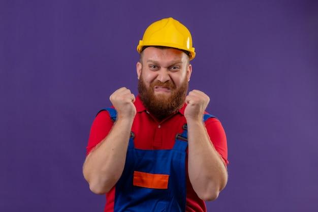 건설 유니폼 및 안전 헬멧에 젊은 수염 작성기 남자 보라색 배경 위에 공격적인 표정으로 화난 얼굴로 미친 미친 떨리는 주먹