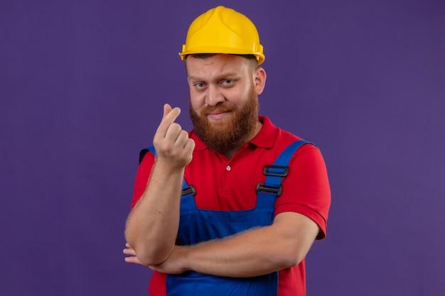 Молодой бородатый строитель в строительной форме и защитном шлеме недоволен, делая денежный жест рукой, потирая пальцы и прося денег на фиолетовом фоне