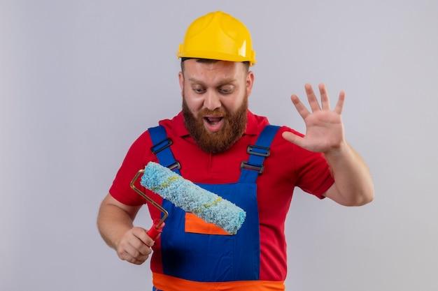 젊은 수염 작성기 남자 건설 유니폼과 페인트 롤러를 들고 페인트 롤러를 들고 놀라게하고 제기 손바닥으로 놀랐습니다.