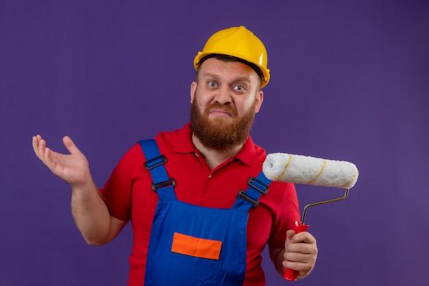 紫色の背景に疑いを持っている混乱した肩をすくめる肩を探しているペイントローラーを保持している建設制服と安全ヘルメットの若いひげを生やしたビルダーの男