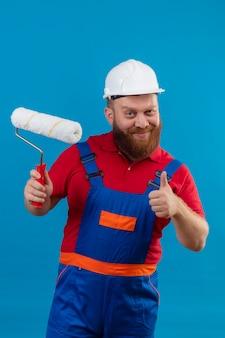 젊은 수염 작성기 남자 건설 유니폼 및 안전 헬멧 들고 페인트 롤러 자신감 보여주는 엄지 손가락 미소