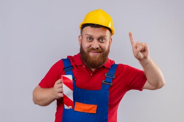 젊은 수염 작성기 남자 건설 유니폼 및 안전 헬멧 들고 테이프 스카치 카메라를보고 웃 고 가리키는 손가락