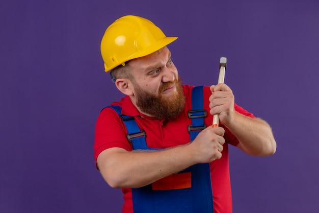紫色の背景の上にハンマーを振ってイライラして見える建設制服と安全ヘルメットの若いひげを生やしたビルダーの男