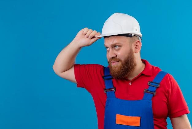 Молодой бородатый строитель в строительной форме и защитном шлеме смотрит в сторону с несчастным лицом, касаясь его шлема
