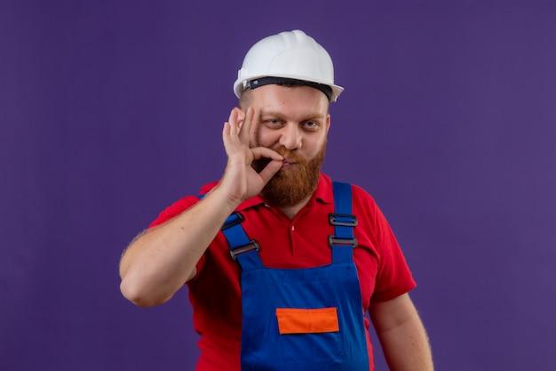 紫色の背景の上にジッパーで口を閉じるような沈黙のジェスチャーを作る自信を持って見える建設制服と安全ヘルメットの若いひげを生やしたビルダーの男