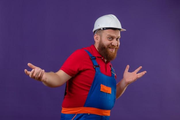 Молодой бородатый строитель в строительной форме и защитном шлеме смущенно пожимает плечами и раскидывает руки на фиолетовом фоне