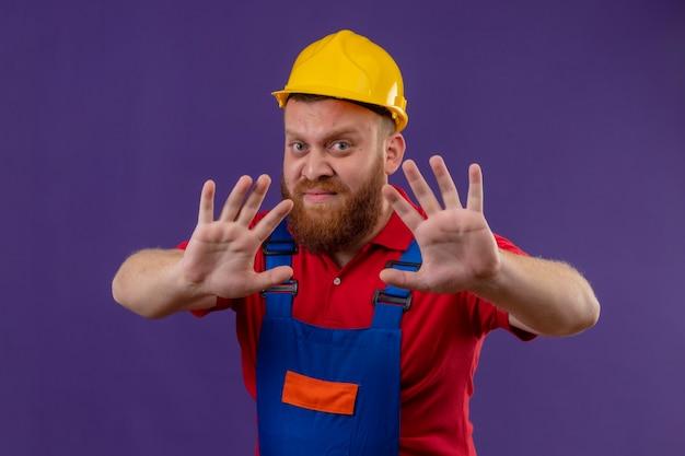 Молодой бородатый строитель в строительной форме и защитном шлеме делает жест защиты отказа с открытыми руками, с выражением отвращения на фиолетовом фоне