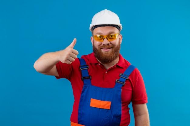 建設制服と安全ヘルメットの若いひげを生やしたビルダーの男ポジティブで幸せな親指を見せて、フレンドリーな笑顔