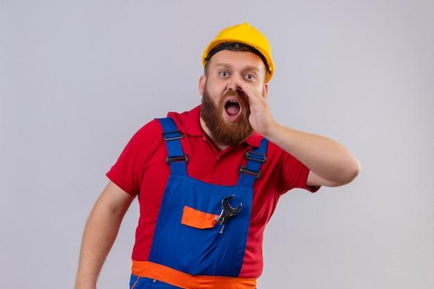 建設制服と安全ヘルメットの若いひげを生やしたビルダーの男は、口の近くの手で誰かを叫んだり、呼び出したりします