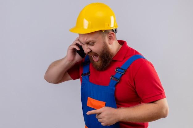攻撃的な表情で携帯電話で話している間、建設制服と安全ヘルメットの若いひげを生やしたビルダーの男が叫んでいます
