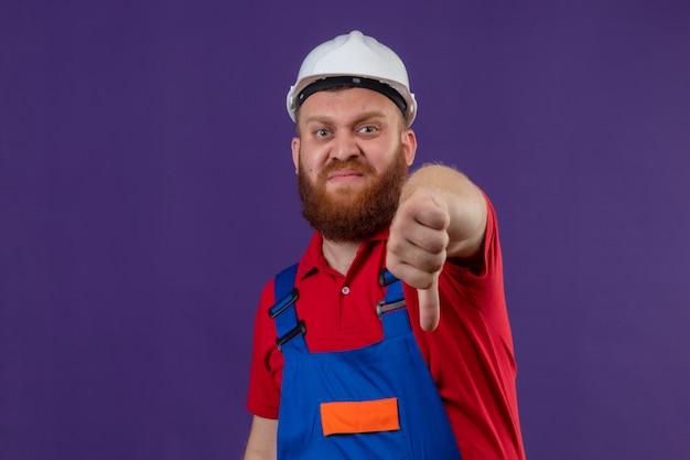 Молодой бородатый строитель в строительной форме и защитном шлеме демонстрирует неприязнь с недовольным лицом, показывая пальцы вниз на фиолетовом фоне