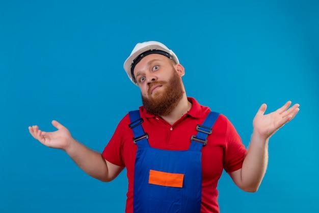 Молодой бородатый строитель в строительной форме и защитном шлеме пожимает плечами, выглядит смущенным и неуверенным, не имея ответа, разводя ладони