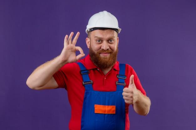 Молодой бородатый строитель в строительной форме и защитном шлеме улыбается счастливым и позитивным, делает хорошо, поет показывает палец вверх на фиолетовом фоне
