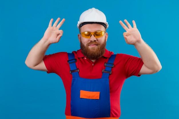 建設制服と安全ヘルメットの若いひげを生やしたビルダーの男は、指で瞑想のジェスチャーをしてリラックスして目を閉じています