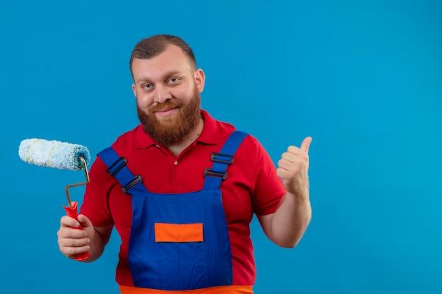 Молодой бородатый строитель в строительной форме, держащий валик с краской, улыбаясь, показывает палец вверх
