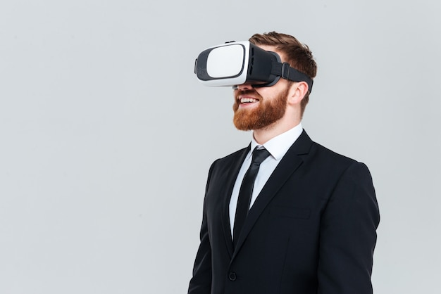 Young bearded business man in black suit using virtual reality device. side view. isolated gray background