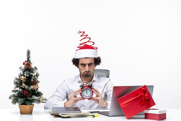 Giovane barbuto uomo d'affari con cappello di babbo natale e mostrando orologio guardando qualcosa di sorpresa e seduto in ufficio su sfondo bianco stock photo