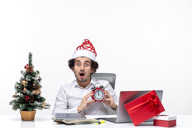 Giovane barbuto uomo d'affari con cappello di babbo natale e mostrando orologio guardando qualcosa di sorpresa e seduto in ufficio su sfondo bianco