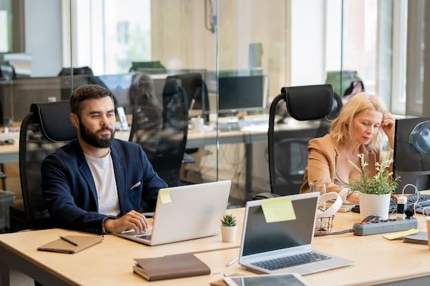Молодой бородатый бизнесмен и зрелая белокурая женщина сидят за столом перед ноутбуками в офисе на открытом воздухе и работают индивидуально