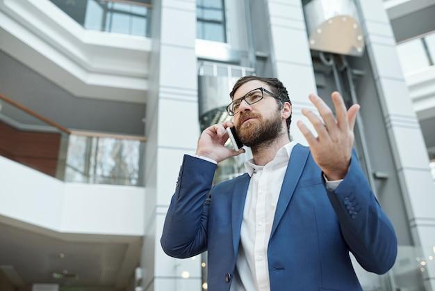 스마트 폰으로 전화하는 동안 동료에게 뭔가를 설명하는 formalwear 및 안경에 젊은 수염 사업가