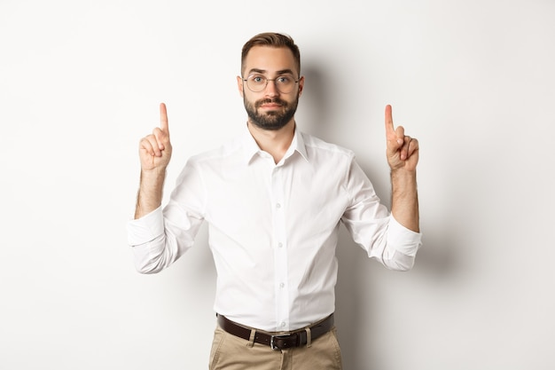 Young bearded businessman pointing fingers up, showing promo offer, standing over white background. copy space