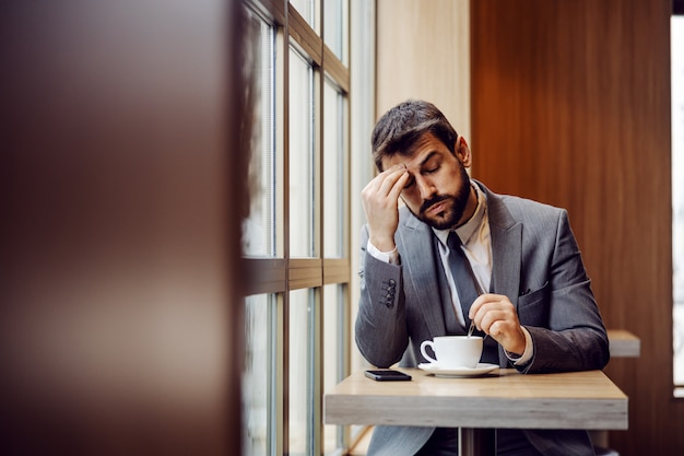 Young bearded businessman sitting in coffee shop next to window and having headache. he thinks morning coffee could help.