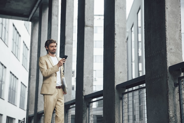 Young bearded businessman in stylish suit solving urgent working moments through modern smartphone while standing outside with laptop in hand