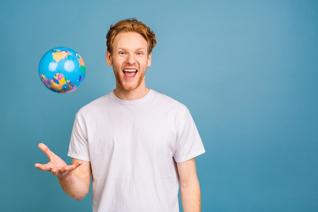 Young bearded businessman wants to explore unknown places, looks at worldwide globe