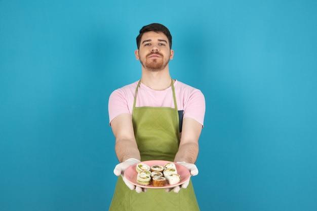 Giovane chef barbuto che tiene i rotoli di torta fresca fatta in casa su un blu.