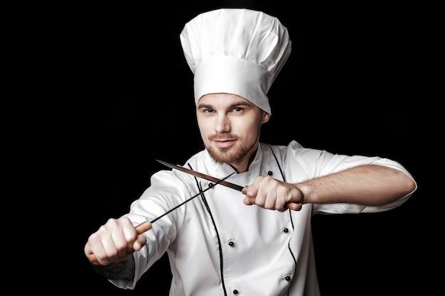 黒の背景に2つのナイフを保持している白い制服を着た若いひげを生やしたシェフ