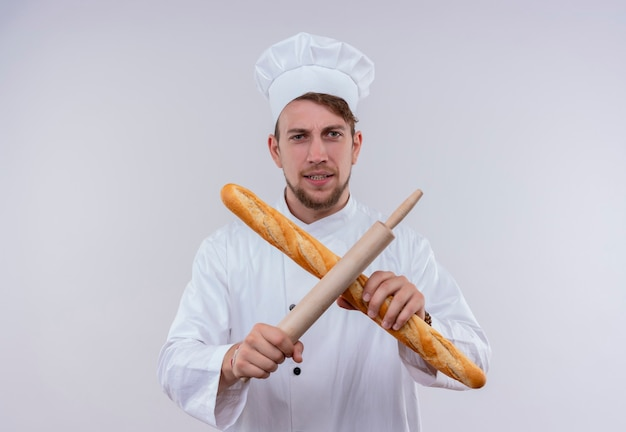 A young bearded chef man wearing white cooker uniform and hat holding baguette bread with rolling pin in x sign while looking on a white wall