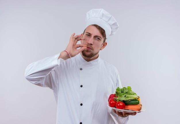 Un giovane chef barbuto uomo che indossa un fornello bianco uniforme e cappello che mostra un gustoso gesto ok mentre si tiene un piatto bianco con verdure fresche come pomodori, cetrioli, lattuga e guardando un