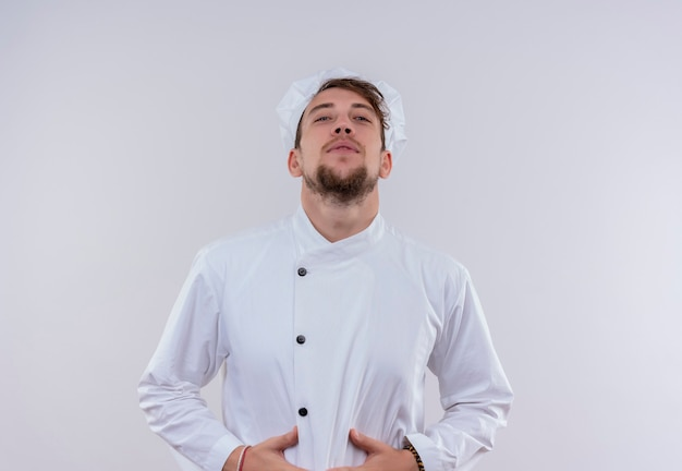 A young bearded chef man in white uniform holding hand on his stomach while looking on a white wall