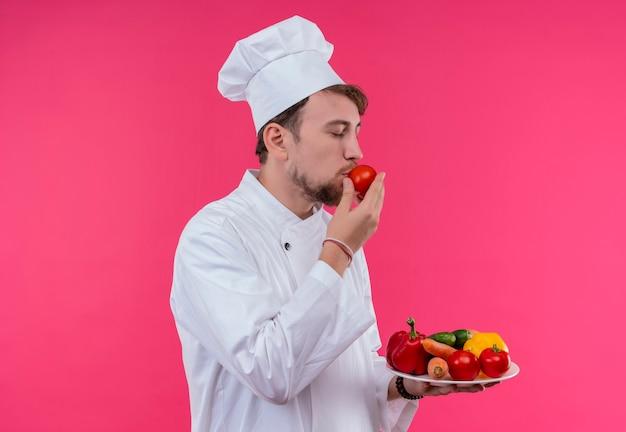 Un uomo giovane chef barbuto in uniforme bianca che tiene un piatto con verdure fresche mentre annusa il pomodoro su una parete rosa