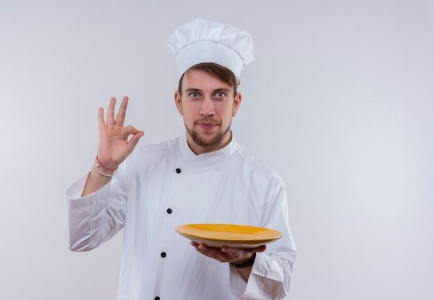 Un giovane chef barbuto in uniforme bianca che tiene piatto giallo e che mostra il gesto del segno giusto mentre guarda su un muro bianco