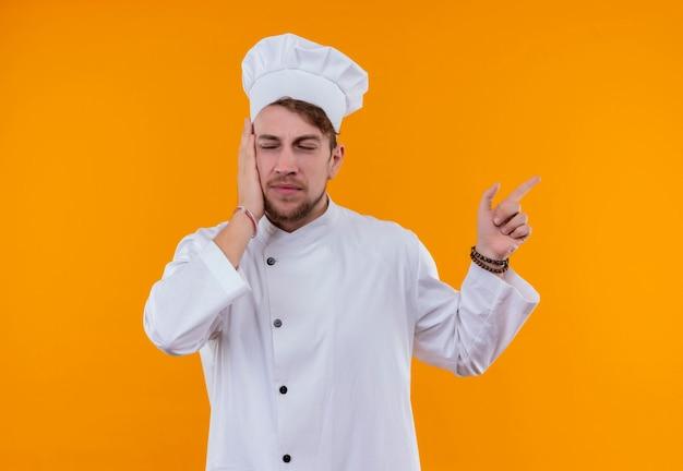 Un uomo giovane chef barbuto in uniforme bianca rivolta verso l'alto con il dito indice mentre si tiene la mano sul viso su una parete arancione