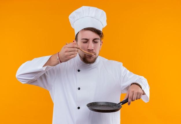 Un giovane uomo barbuto chef in uniforme bianca degustazione delizioso piatto tenendo il cucchiaio di legno e la padella su una parete arancione